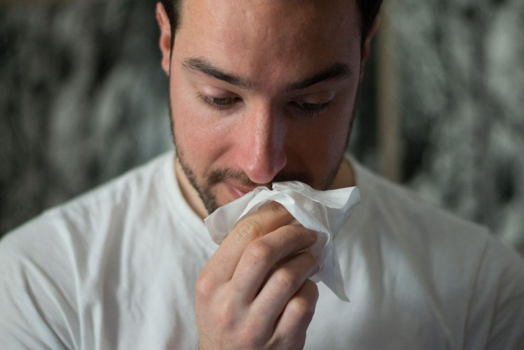 Man sneezes. Is sneezing a symptom of COVID?