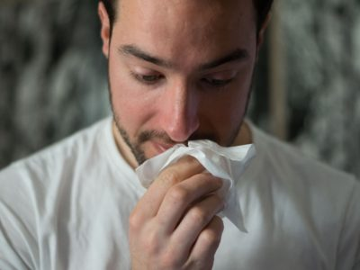 Man sneezes. Is sneezing a symptom of COVID?